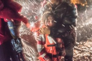 LESVOS - A volunteer holds and comforts a Syrian girl who is in shock.