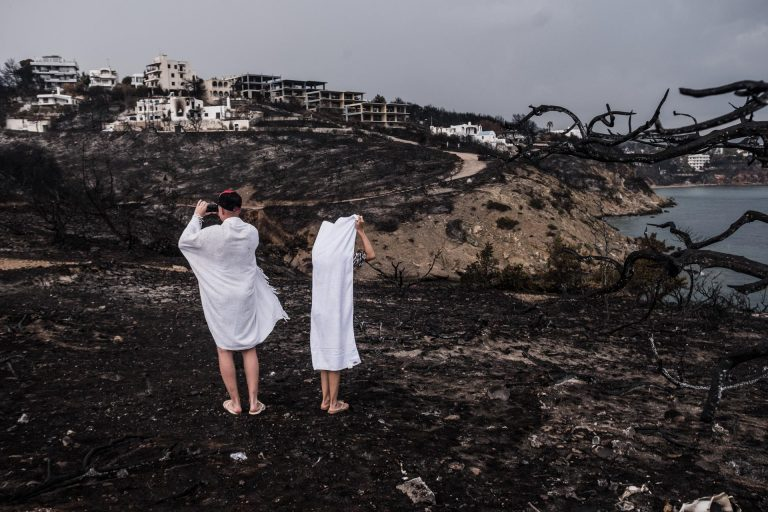 Mati, Athens, Greece, | November 28, 2018 | Two Russian tourist who just went for a swim are looking at the damage the forest fires have caused.