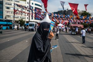 Istanbul, Turkey, June 21, 2018 | PHOTO #4  | A muslin woman is handing out pro-AKP flyers in Istanbul, a few days prior to the 2018 elections. Photo: Joris van Gennip
