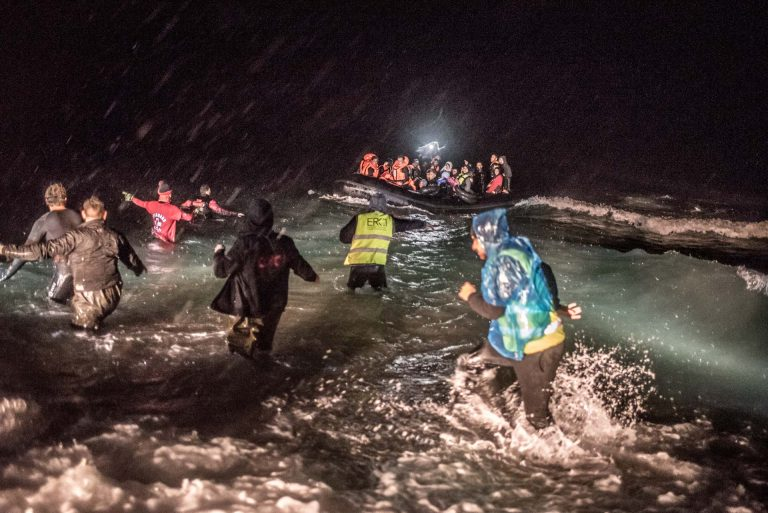 LESVOS - Volunteers rush towards the dinghy to guide it onto the beach. Due to heavy current the travel took 7 hours instead of the promised 1.5.